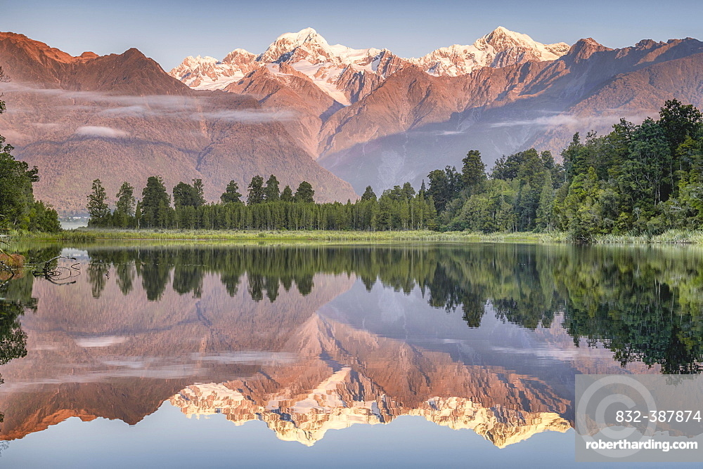 Snowy mountain peaks of Mount Cook and Mount Tasman reflected in Lake Matheson in the evening light, Westland National Park, Fox Glacier, Whataroa, West Coast, New Zealand, Oceania
