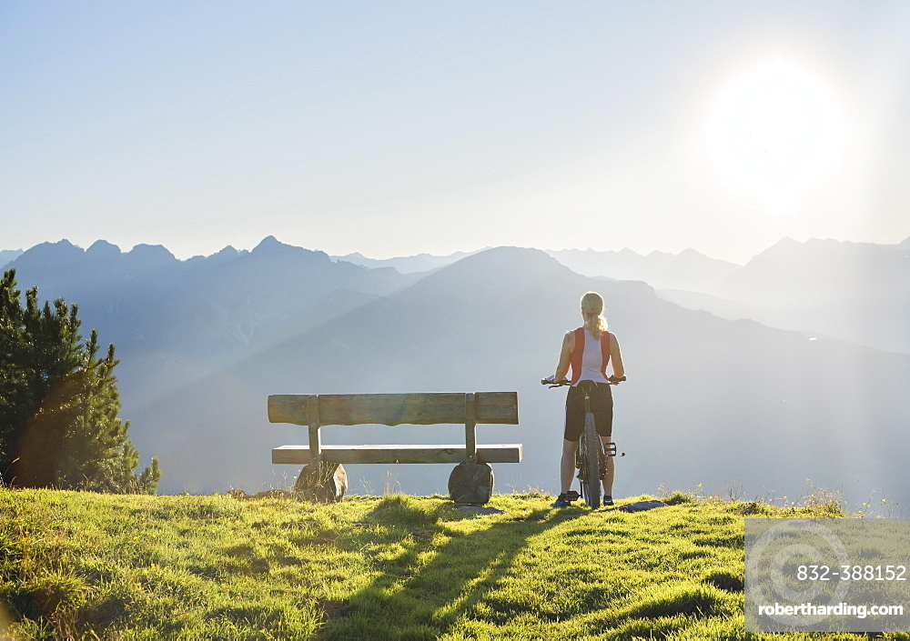 Mountain biker stands with MTB next to a wooden bench and looks into the wide light-flooded mountain landscape, Patscherkofel, Patsch, Tyrol, Austria, Europe
