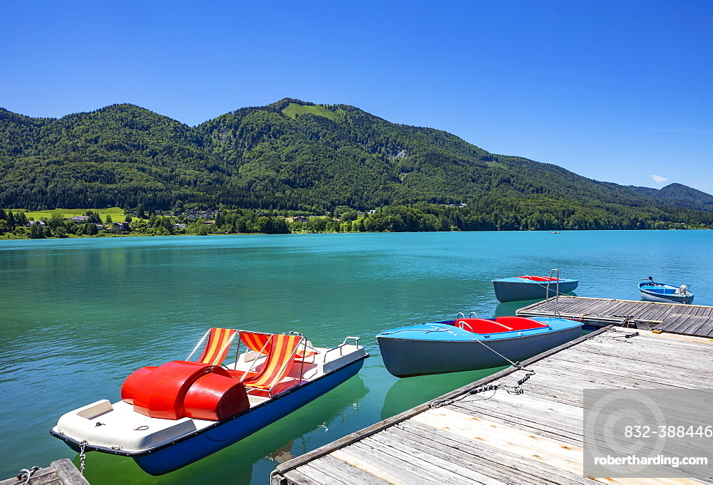 Pedal boat and electric boats at the landing stage on the lake promenade, behind it the Filbling, Fuschlsee, Fuschl am See, Salzkammergut, Province of Salzburg, Austria, Europe