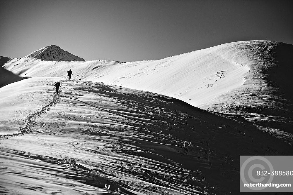 Two tourists on the approach under Rakoń peak winter road, Tatra National Park, Poland, Europe