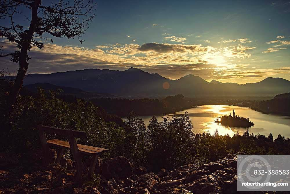 A bench for lovers with a view of the rising sun on Lake Bled, Bled, Slovenia, Europe