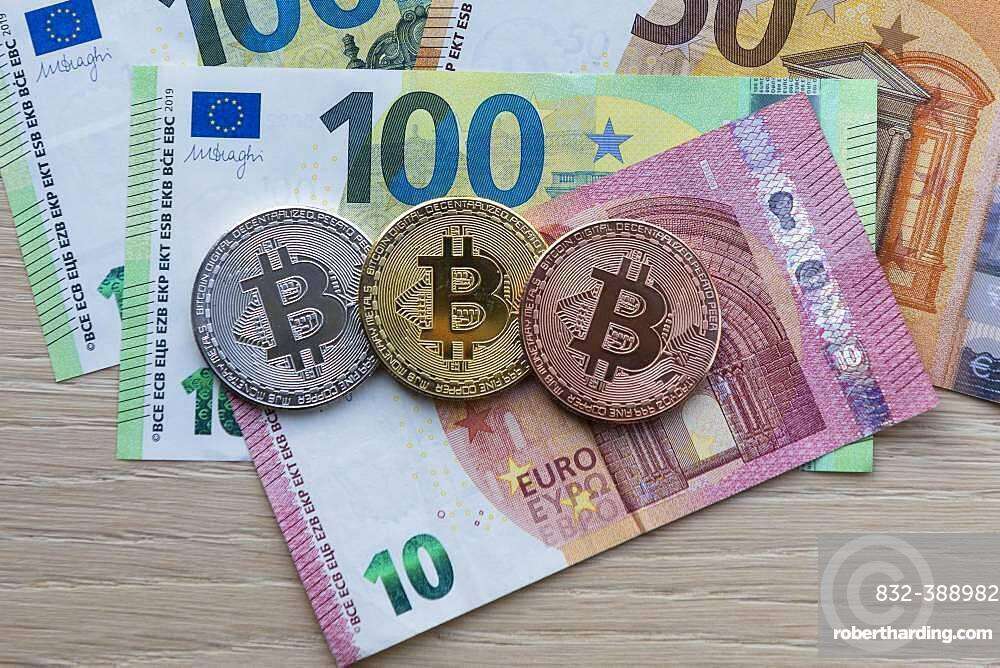 Symbol image digital currency, physical coin Bitcoin, silver, gold, bronze, on euro banknotes