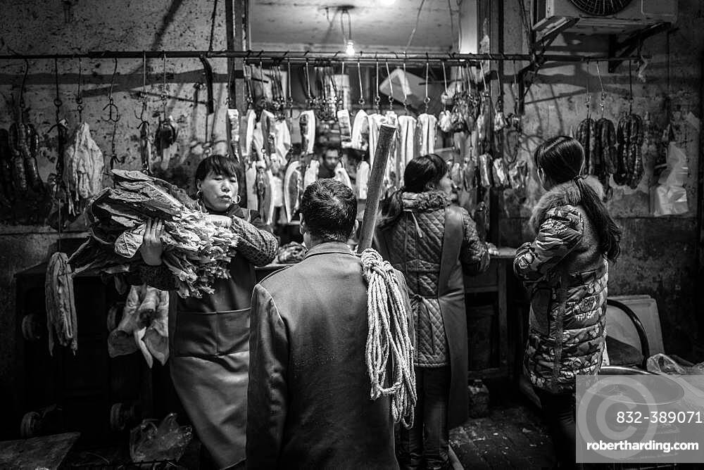 Day labourer in front of a butcher's shop in a market in the centre of Chongqing, from his wages he can only buy the cheap pieces of meat, Chongqing, China, Asia