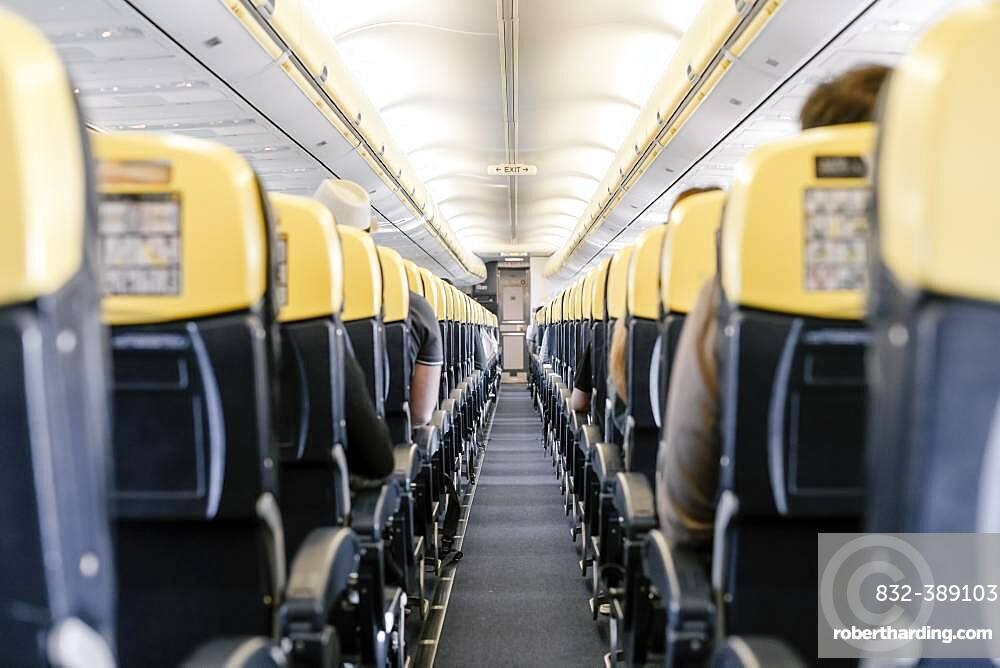 Empty corridor in the airplane with all passengers sitting down