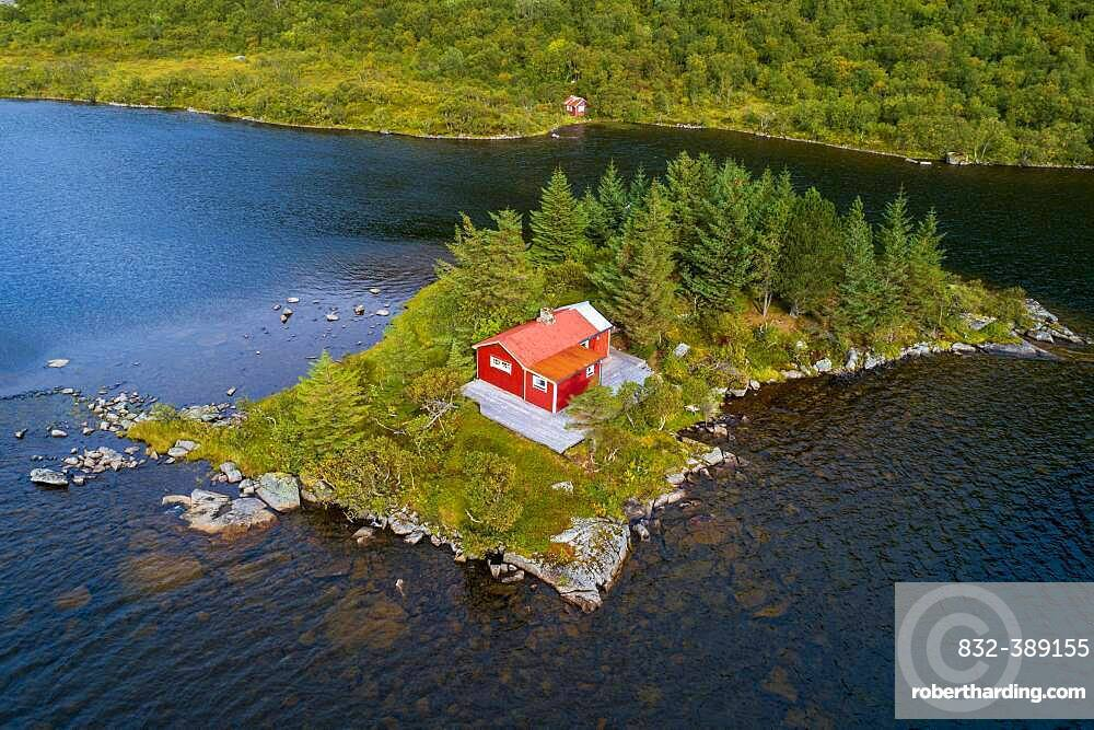 Red wooden cabin on a small island in a lake, Vestvagoy, Nordland, Lofoten, Norway, Europe