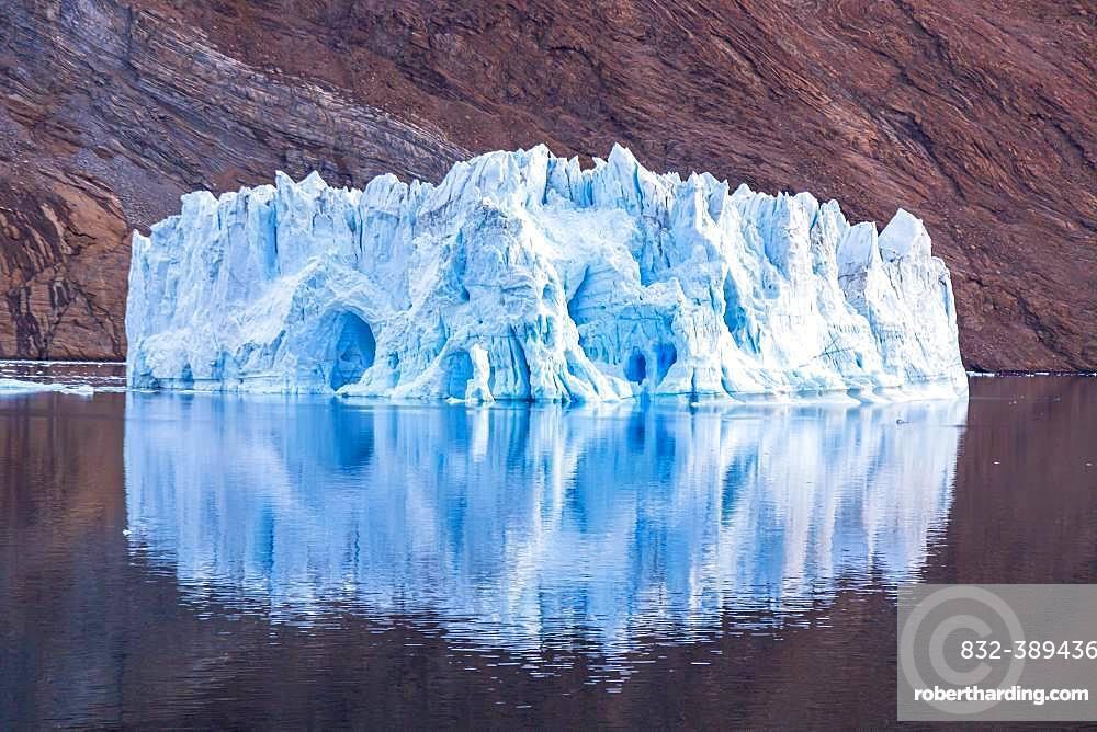 Iceberg in front of rock in fjord, Kaiser-Franz-Joseph-Fjord, east coast Greenland, Denmark, Europe