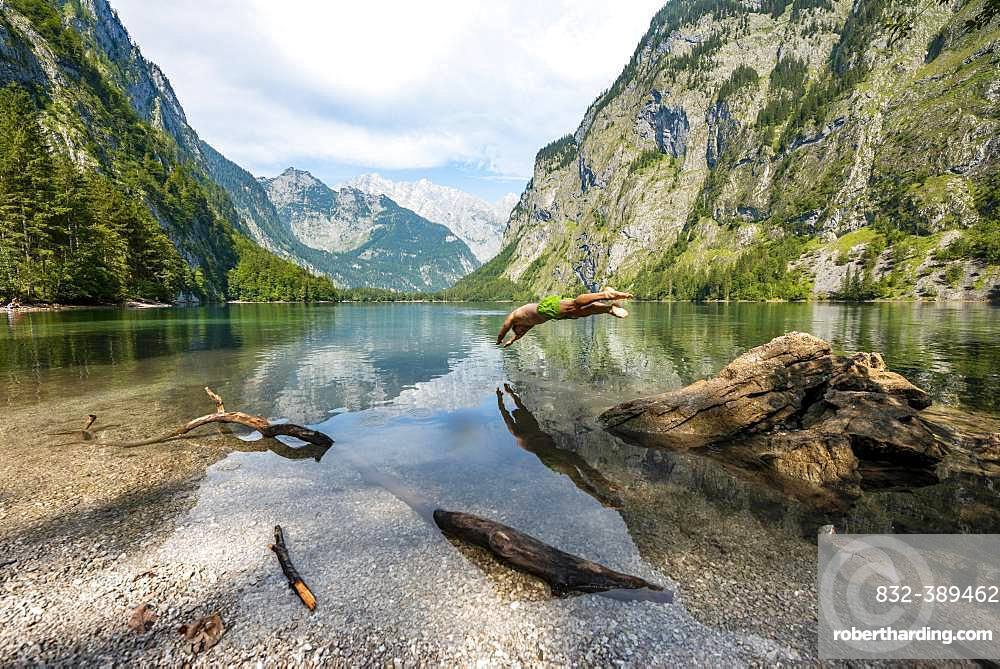 Young man jumps into lake, bathes in mountain lake, mountains are reflected in Obersee, behind Watzmann, salet at Koenigssee, Berchtesgaden National Park, Berchtesgadener Land, Upper Bavaria, Bavaria, Germany, Europe