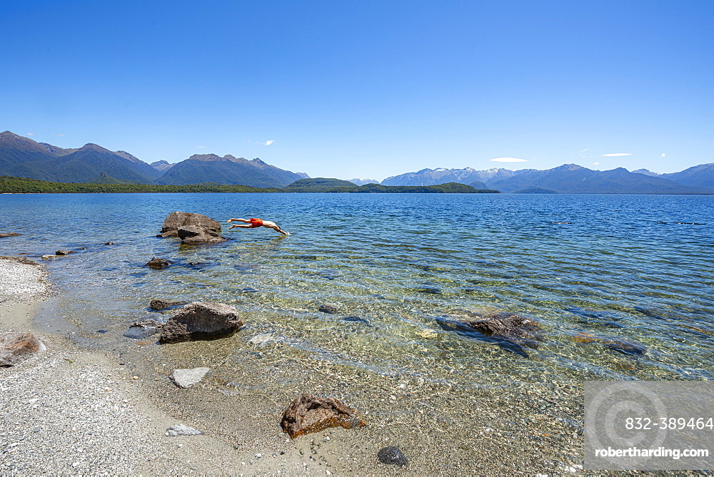 Young man jumps from stone into water, Beach Frasers Beach, Lake Manapouri, Manapouri, South Island, New Zealand, Oceania