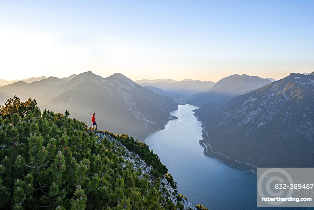 Young man looking over mountain landscape, view from the top of the Baerenkopf to the Achensee, left Seekarspitze and Seebergspitze, Karwendel, Tyrol, Austria, Europe