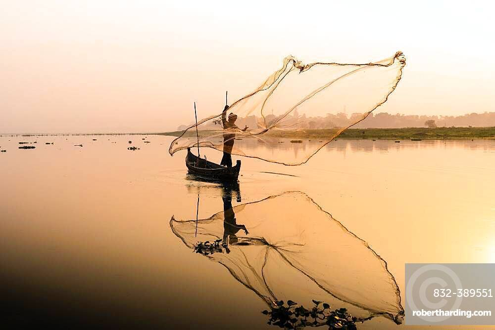 Fisherman with boat on Taung Tha Man Lake casts a fishing net for sunrise, reflection in the water, Thaung Tha Man Lake, Mandalay, Myanmar, Asia
