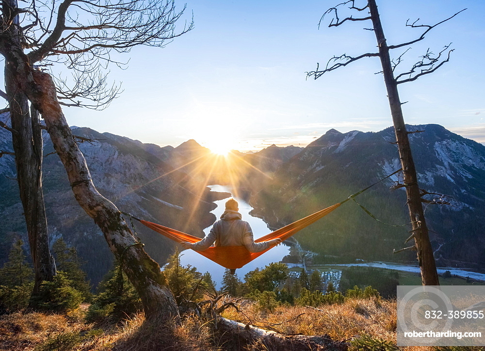 Young man sitting in a red hammock, panoramic view of mountains with lake, sun star, sunset, Plansee, Tyrol, Austria, Europe