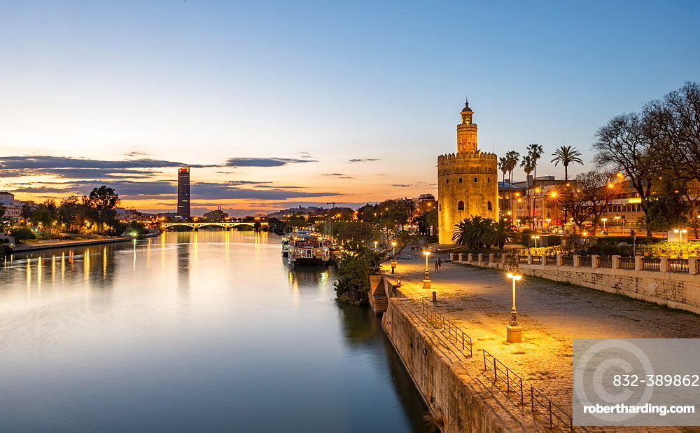 View over the river Rio Guadalquivir with Torre del Oro, promenade and Puente de Triana, in the back Torre Sevilla, sunset, blue hour, Sevilla, Andalusia, Spain, Europe