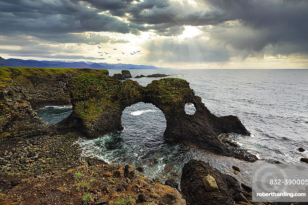 Eroded cliff at the Atlantic Ocean with Gatklettur and dramatic cloud formation, Arnarstapi, Faxafloi, Snaefellsnes Peninsula, Iceland, Europe