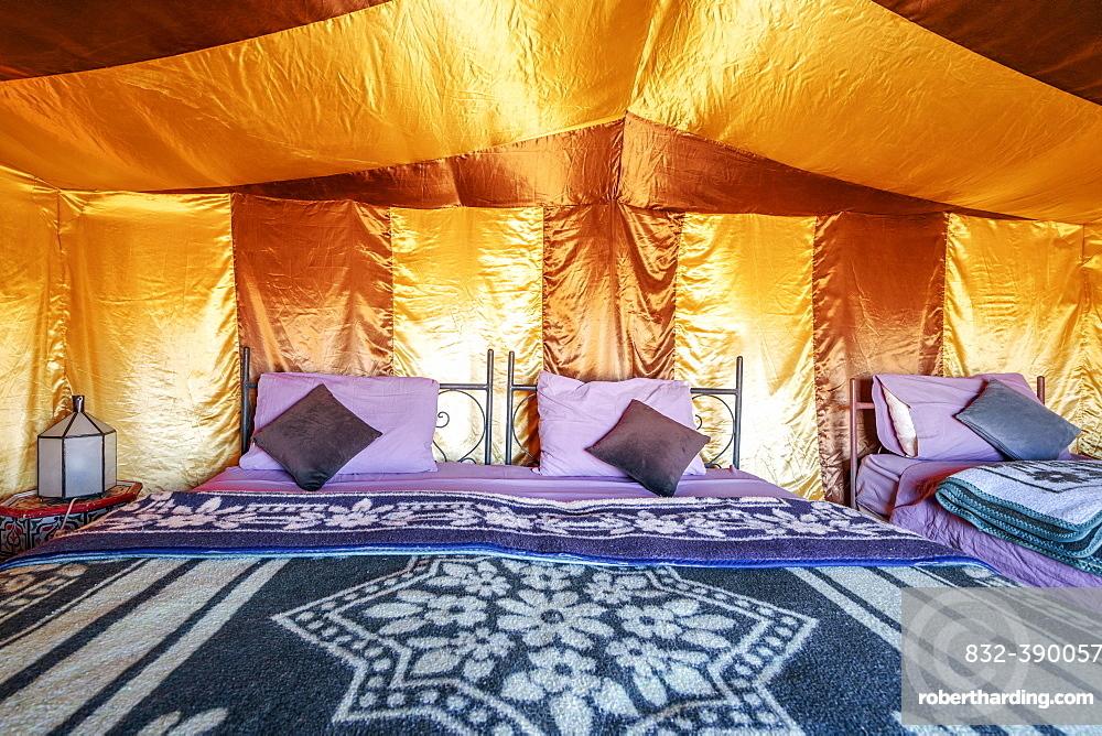 Three beds inside elegant tent set on Sahara desert, Morocco, Africa