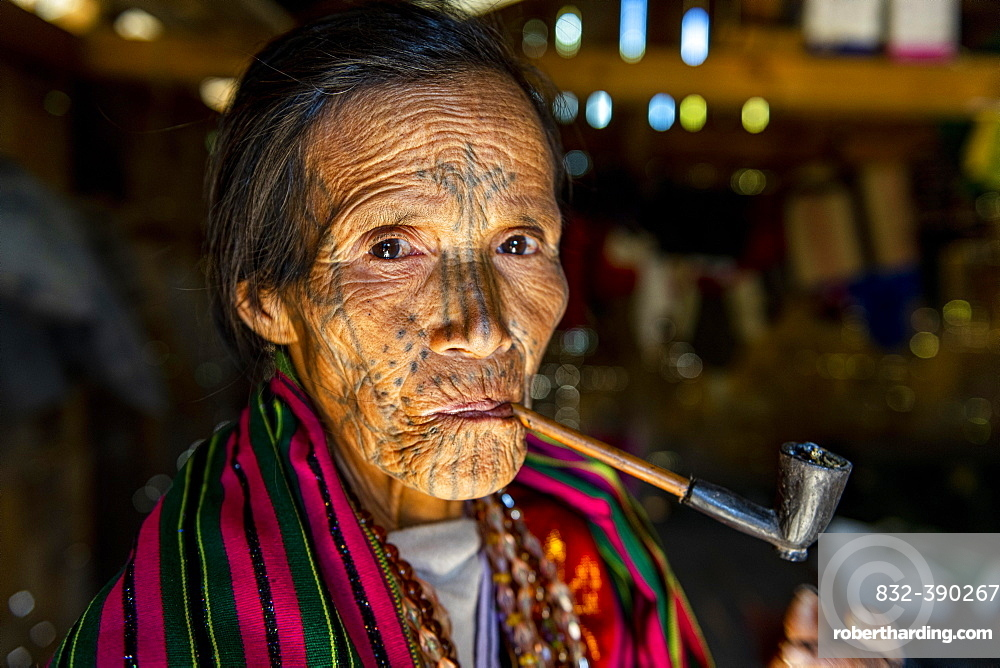 Chin woman with spiderweb tattoo smoking a pipe, Mindat, Chin state, Myanmar, Asia