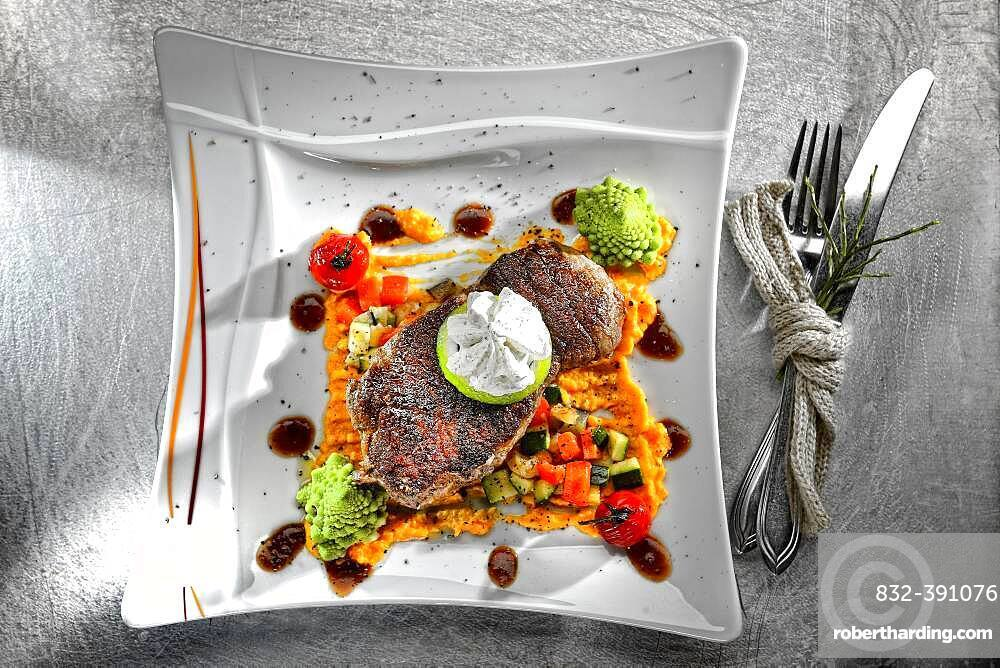 Rump steak, herb butter and vegetables, served on a plate