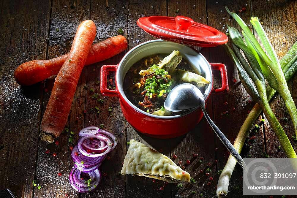 Maultaschen soup in the pot, Maultaschen in the broth, decorated with fresh vegetables