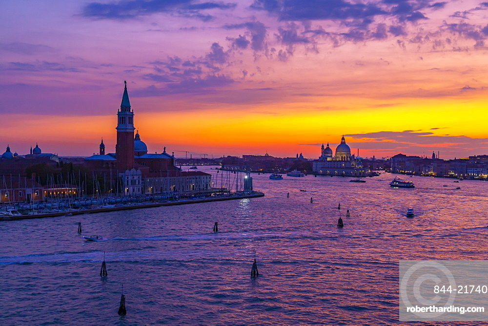 View of Venice skyline and red sky from cruise ship at dusk, Venice, Italy, Europe