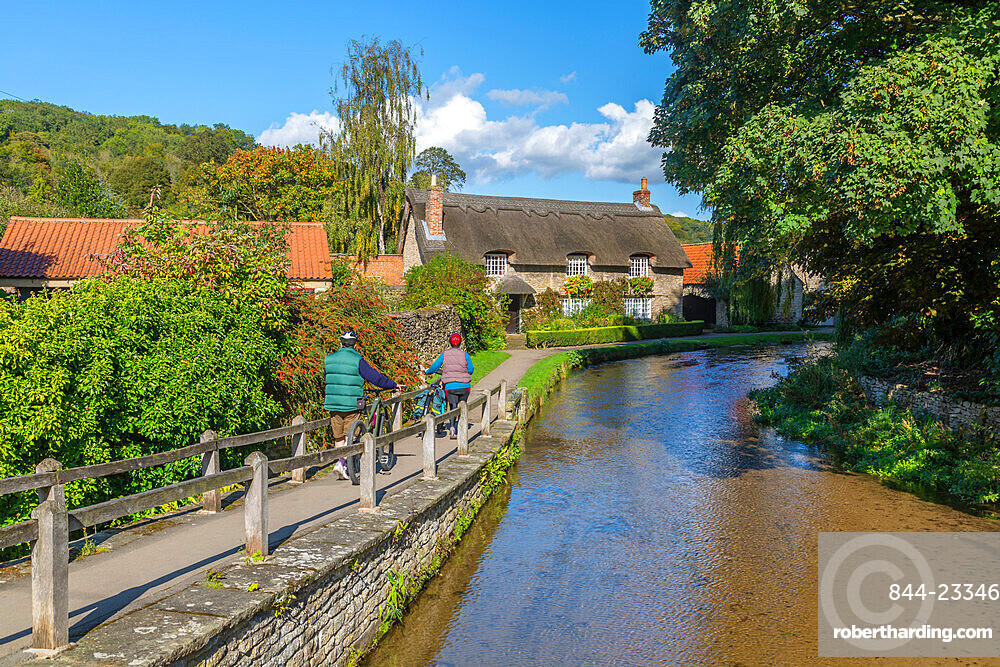 View of cyclists, riverside thatched cottage and Thornton Beck, Thornton Dale, North Yorkshire, England, United Kingdom, Europe