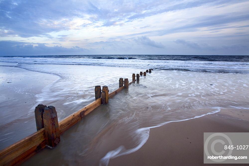 Groynes and receding tide on Alnmouth Beach at dusk, Northumberland, England, United Kingdom, Europe