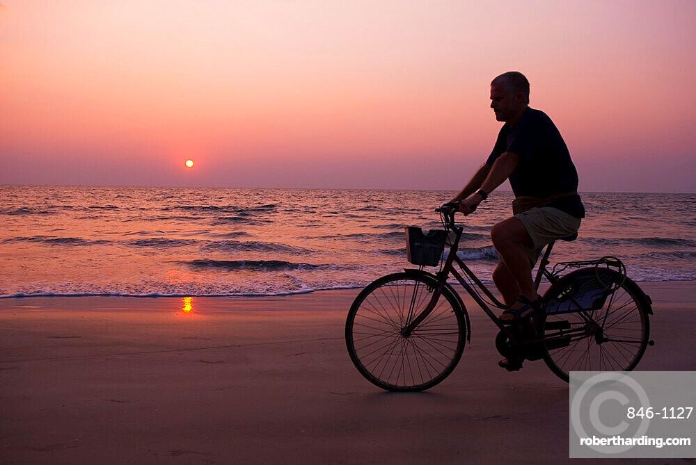 Sunset and cyclist, Goa, India, Asia