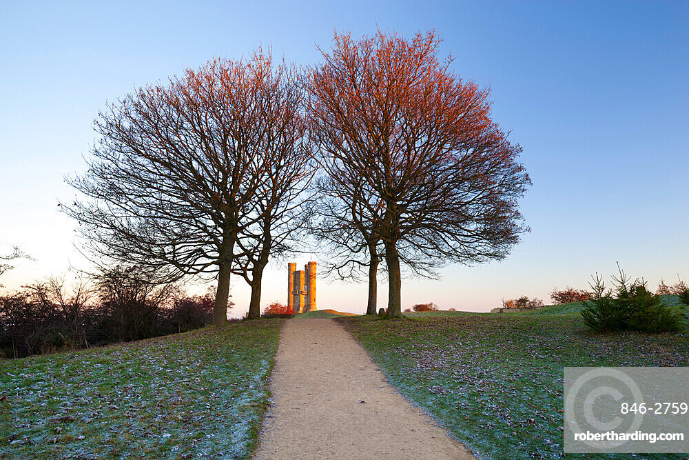 Broadway Tower framed by trees in winter frost at sunrise, Broadway, Cotswolds, Worcestershire, England, United Kingdom, Europe