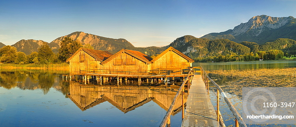 Boathouses at Kochelsee Lake at sunset, Herzogstand and Heimgarten Mountains, Upper Bavaria, Bavaria, Germany, Europe