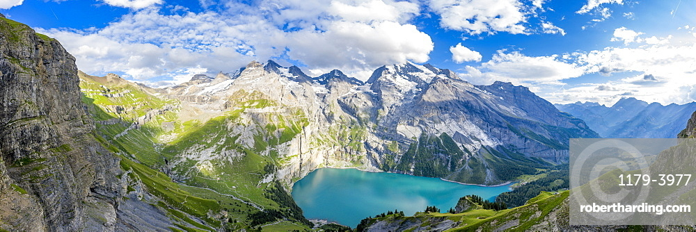 Aerial panoramic of Oeschinensee lake surrounded by woods in summer, Bernese Oberland, Kandersteg, Canton of Bern, Switzerland, Europe