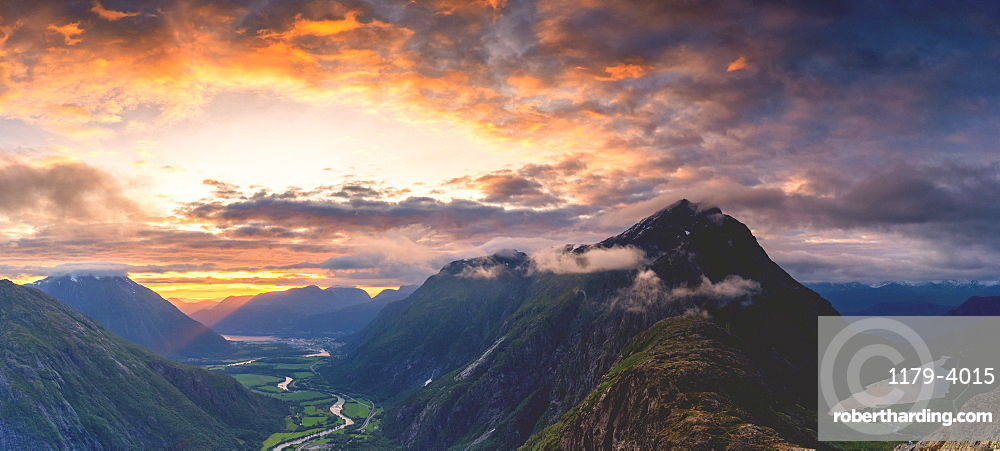 Fiery sky at sunset over Romsdalen and Venjesdalen mountains seen from Romsdalseggen Ridge, Andalsnes, More og Romsdal, Norway (drone)