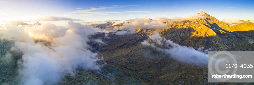 Aerial panoramic of sea of clouds over Pizzo Tambò and bends of the Spluga Pass road, Valle Spluga, Valtellina, Lombardy, Italy