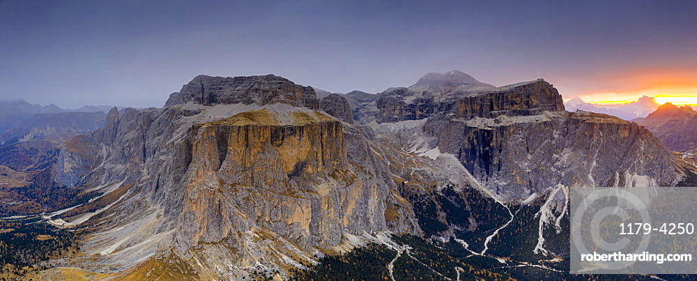 Woods in autumn at feet of Sass Pordoi and Sella mountain at dawn, aerial view, Passo Sella, Dolomites, South Tyrol, Italy