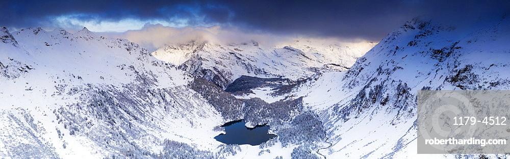 Aerial panoramic of Lake Cavloc and snowy woods, Bregaglia Valley, canton of Graubunden, Engadine, Switzerland