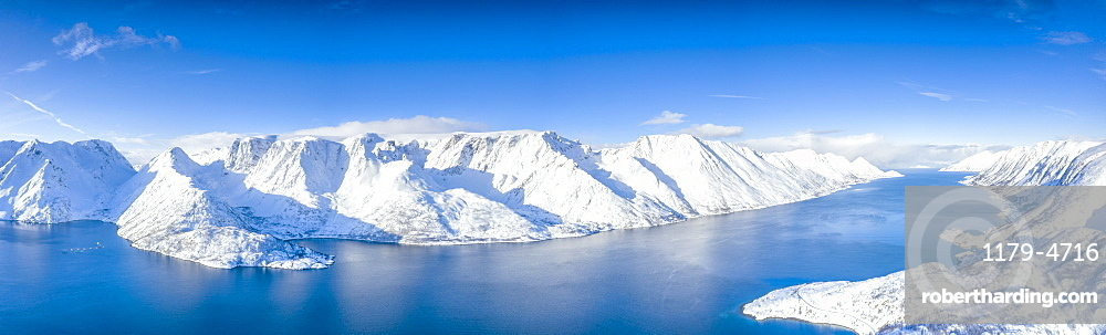 Aerial view of snow capped mountains and fjord during the cold arctic winter, Oksfjord, Troms og Finnmark, Northern Norway