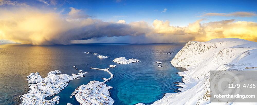 Burning sky at sunrise over the cold sea and Sorvaer village covered with snow, Soroya Island, Hasvik, Troms og Finnmark, Arctic, Norway, Scandinavia, Europe