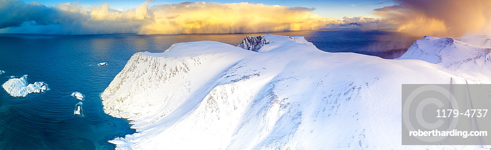 Aerial view of sunrise on snow capped mountains and blue arctic sea, Sorvaer, Soroya Island, Hasvik, Troms og Finnmark, Arctic, Norway, Scandinavia, Europe