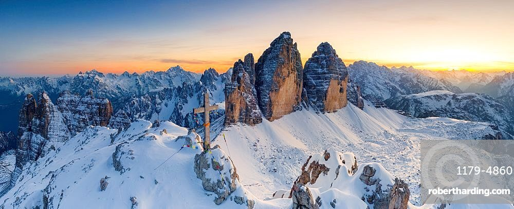 Summit cross on snow capped Monte Paterno with Tre Cime Di Lavaredo on background at sunset, Sesto Dolomites, South Tyrol, Italy