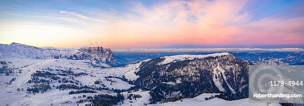 Sunrise over Sciliar Massif and Compatsch village covered with snow, aerial view, Seiser Alm, Dolomites, South Tyrol, Italy