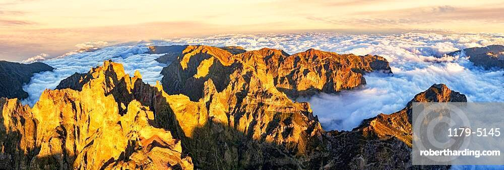 Aerial panoramic of Pico das Torres and Pico do Arieiro mountains in a sea of clouds at sunset, Madeira, Portugal