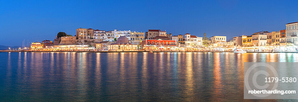 Panoramic of the illuminated old town and Venetian harbour of Chania at dusk, Crete, Greece