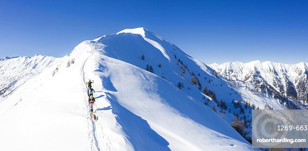 A team of three skiers advances on the mountain ridge, Mount Meriggio, Valtellina, Lombardy, Italy, Europe