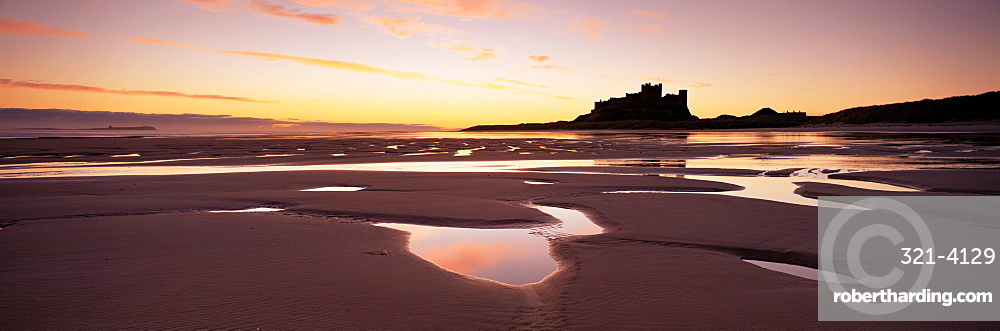 Bamburgh castle in silhouette at sunrise, with rock pools on empty beach, Northumberland, England, United Kingdom, Europe