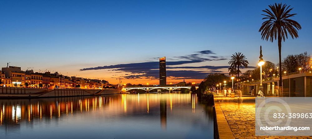 View over the river Rio Guadalquivir with illuminated bridge Puente de Triana and promenade, in the back skyscraper Torre Sevilla, sunset, blue hour, Sevilla, Andalusia, Spain, Europe