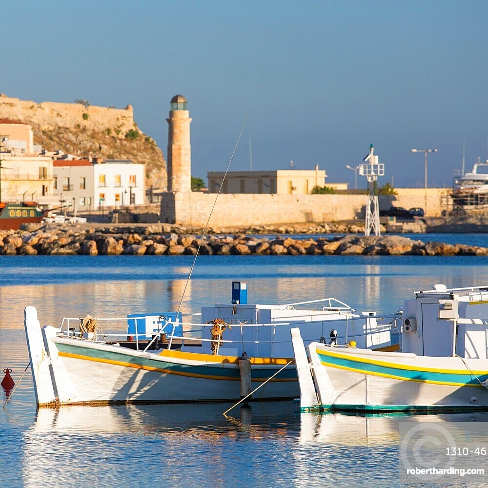 Fishing boats moored in the bay, early morning, historic lighthouse in background, Rethymno (Rethymnon), Crete, Greek Islands, Greece, Europe
