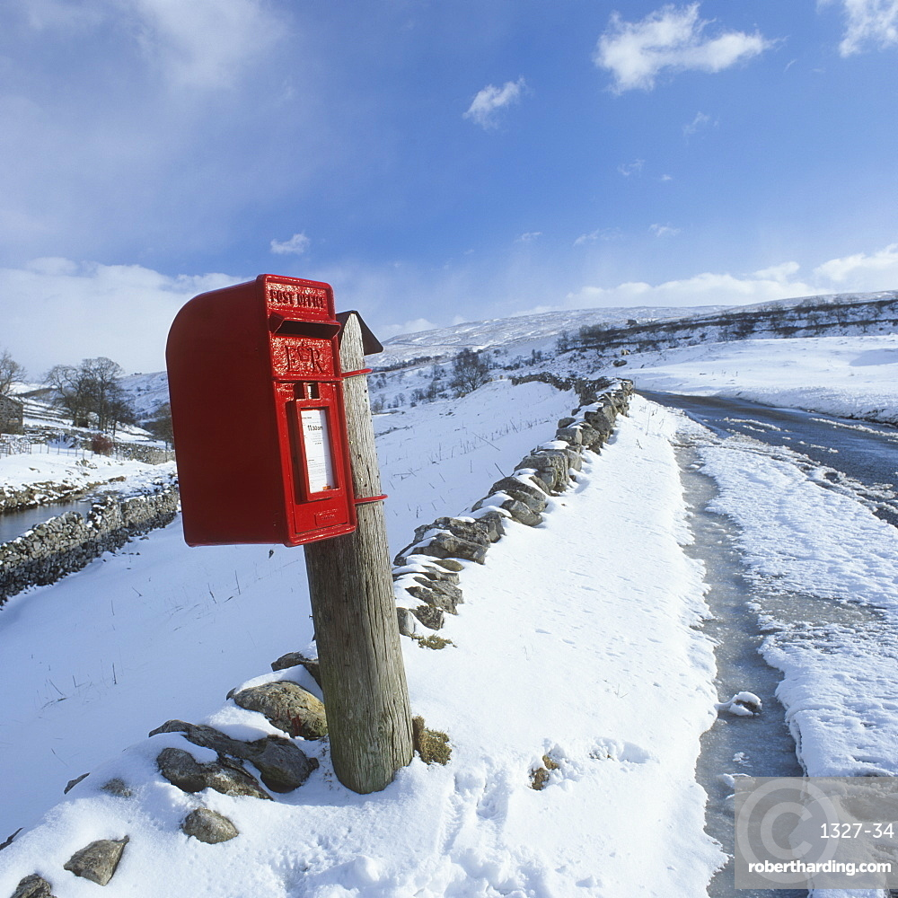 Traditional Red Postbox in a rural setting in the snow, North Yorkshire, England, United Kingdom, Europe