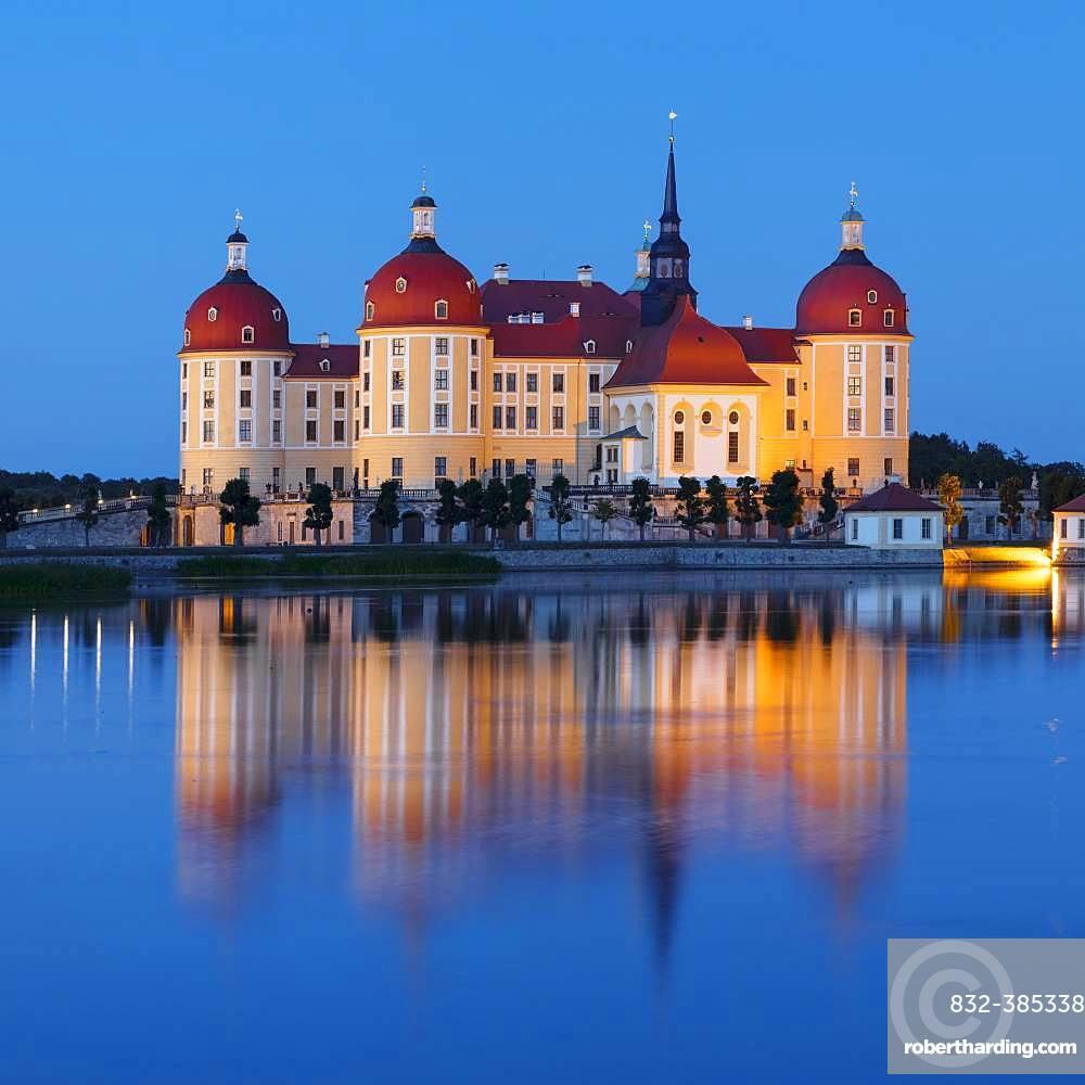 Illuminated Moritzburg Castle at dusk, water reflection in the lake, Saxony, Germany, Europe