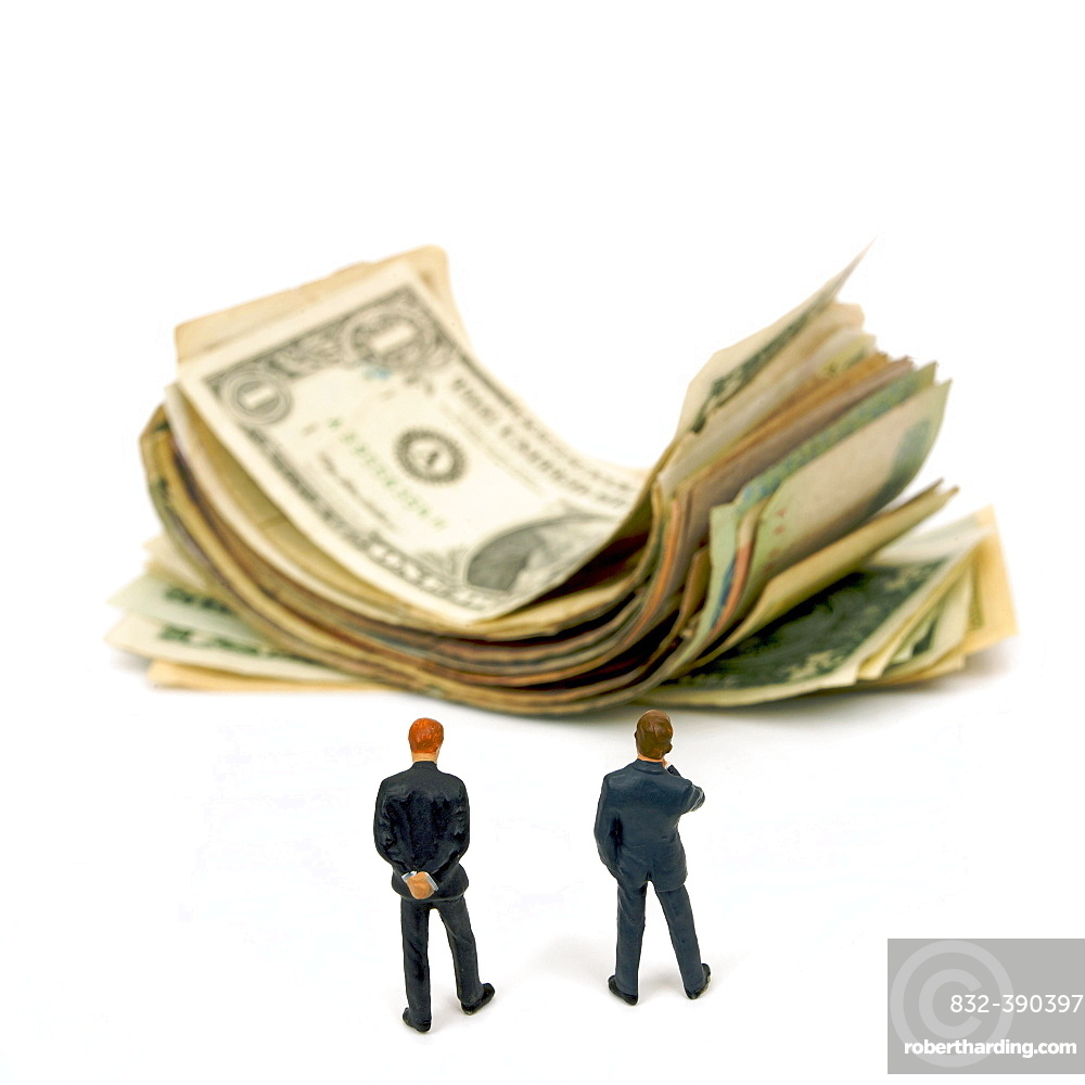 Businessmen and pile of banknotes