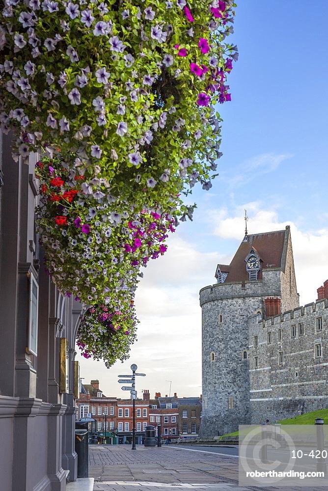 Hanging flowers in Windsor high street with Windsor Castle in the background, Windsor, Berkshire, England, United Kingdom, Europe