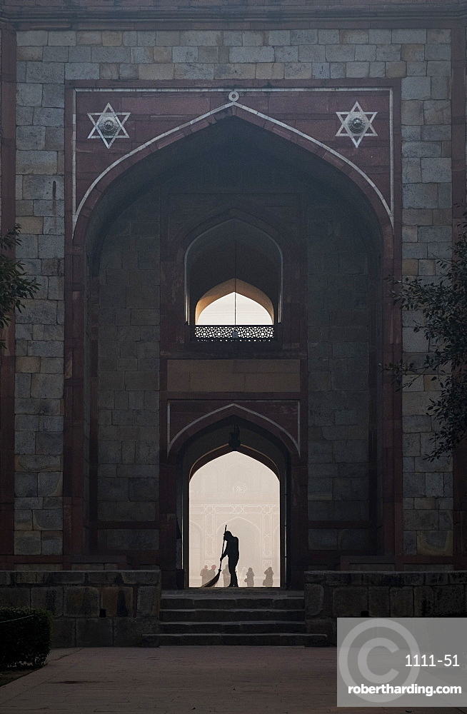 Silhouette of man sweeping under arch of Humayun's Tomb in Delhi, India, Asia