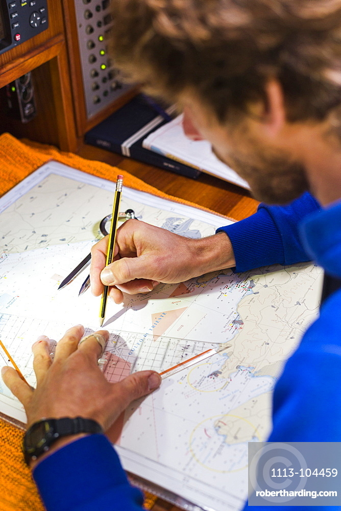 Skipper planing a route on a nautical chart at a sailing boat, Pula, Istria, Croatia