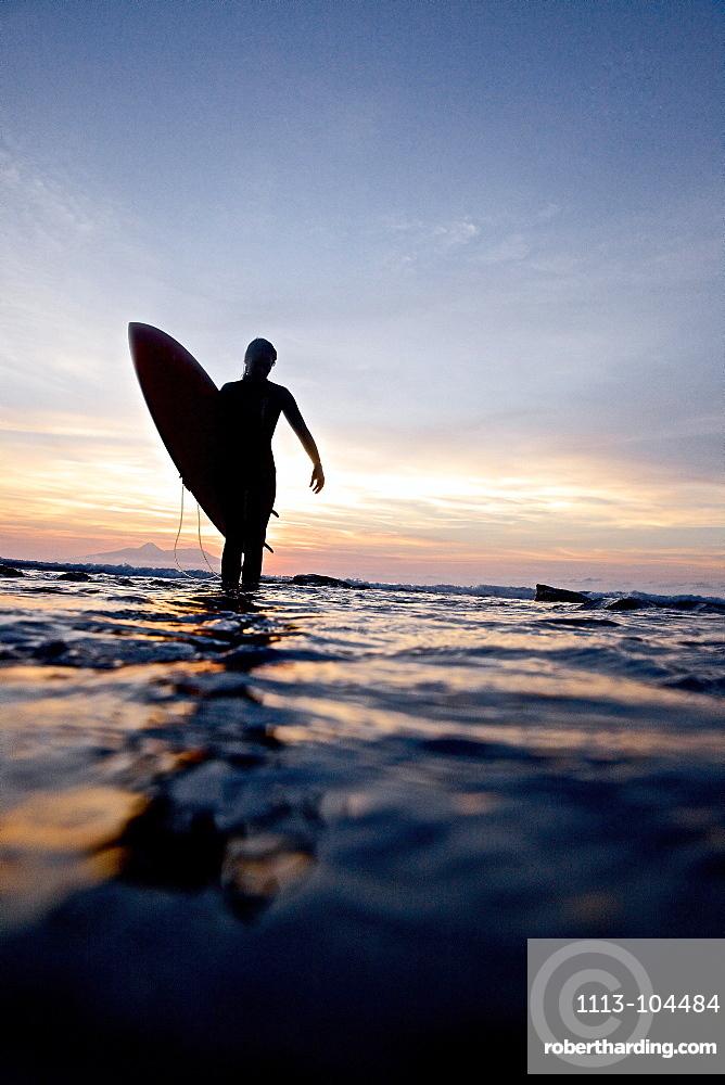 Female surfer carrying surfboard, Praia, Santiago, Cape Verde